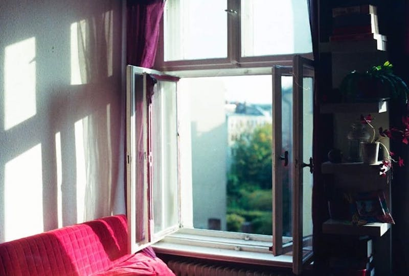 Wide-open casement window with sun shining in on a red sofa.