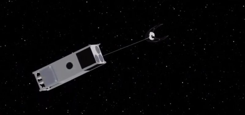 A boxlike spacecraft in orbit with a line going to a piece of space debris, against a black background.
