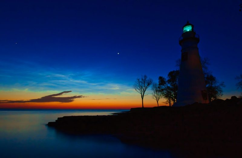 A twilight scene, with a lighthouse, and Venus blazing in the sky.