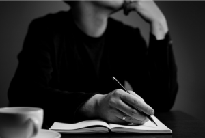 The upper torso and hand (holding a pen) of a person thinking and writing.