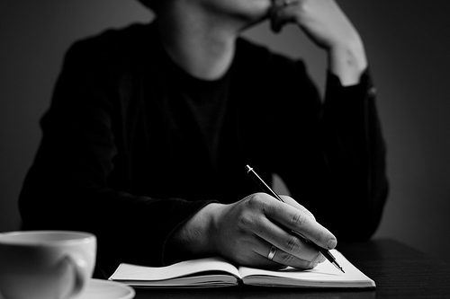 The upper torso and hand (holding a pen) of a person thinking and writing in a journal.