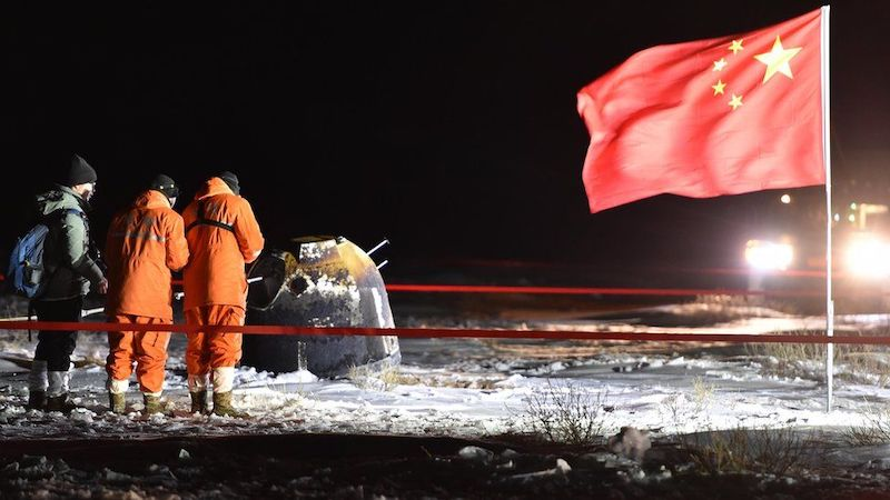 Chinese flag flies beside capsule on snowy ground with people inside red tape barrier around it.