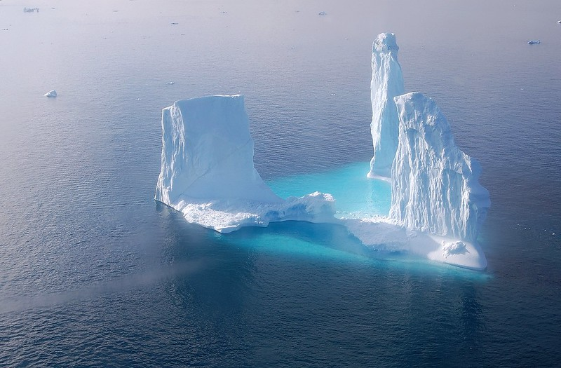 Towers of white ice arising from submerged pale blue base in blue sea.