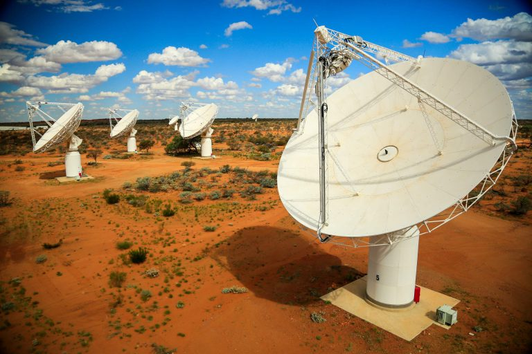Four radio telescopes dishes in barren red desert terrain with blue sky and puffy clouds.
