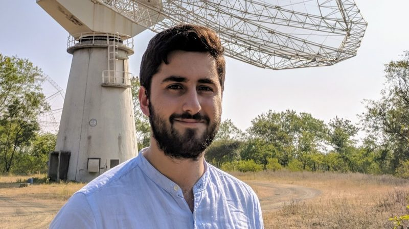 Smiling bearded man standing outside in front of a radio telescope.