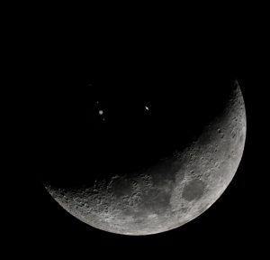 Crescent moon with two bright dots appearing on dark side.