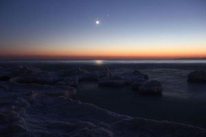 multicoloured sky with ice in foreground, bright crescent moon with earthshine and two bright dots top right.