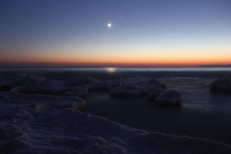 Multicolored sky with icy sea in foreground, bright moon and two bright dots near it.