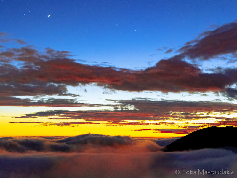 Wispy white in front of dark mountains, yellow and blue sky with red clouds and 2 bright dots in upper left corner.