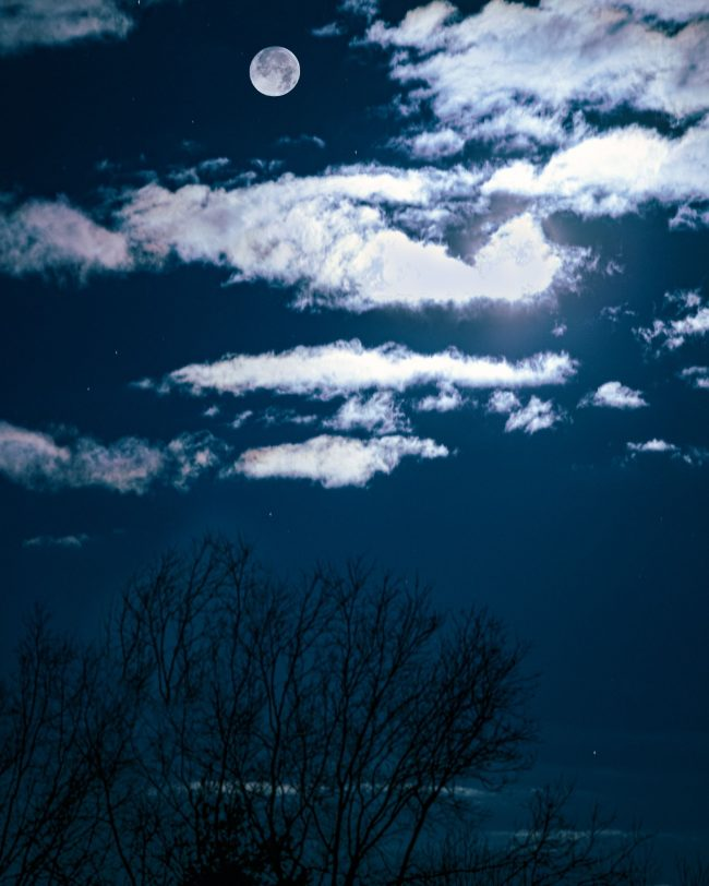 Full moon floats in the midst of white clouds in a dark blue sky above bare trees.