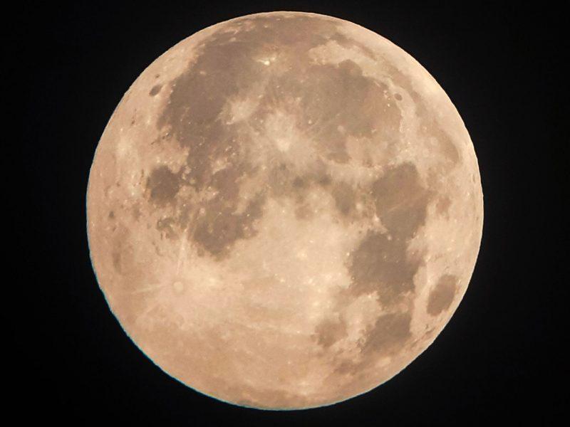 Closeup of the full moon, looking pinkish-yellowish.