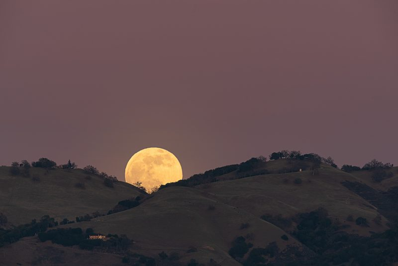 Full yellow moon peeps out from valley between two scrub-covered hills.