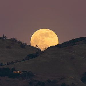 Full moon behind California hills.