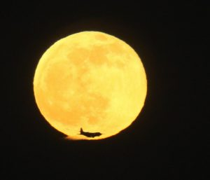Full moon with an airplane in the foreground.