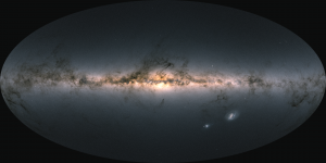 Bright, colorful horizontal formation of stars with other dark wispy tendrils and two other bright ovals.