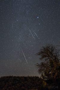 5 meteors streak through a starry sky.