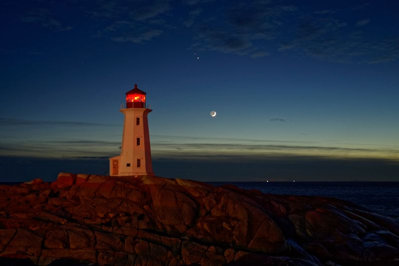 Lighthouse in front of water and sky with crescent moon and two bright dots.