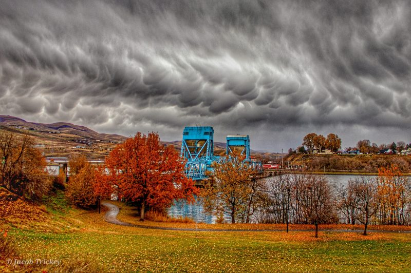 Low-hanging dark gray clouds bulging downward over a blue bridge across a river.
