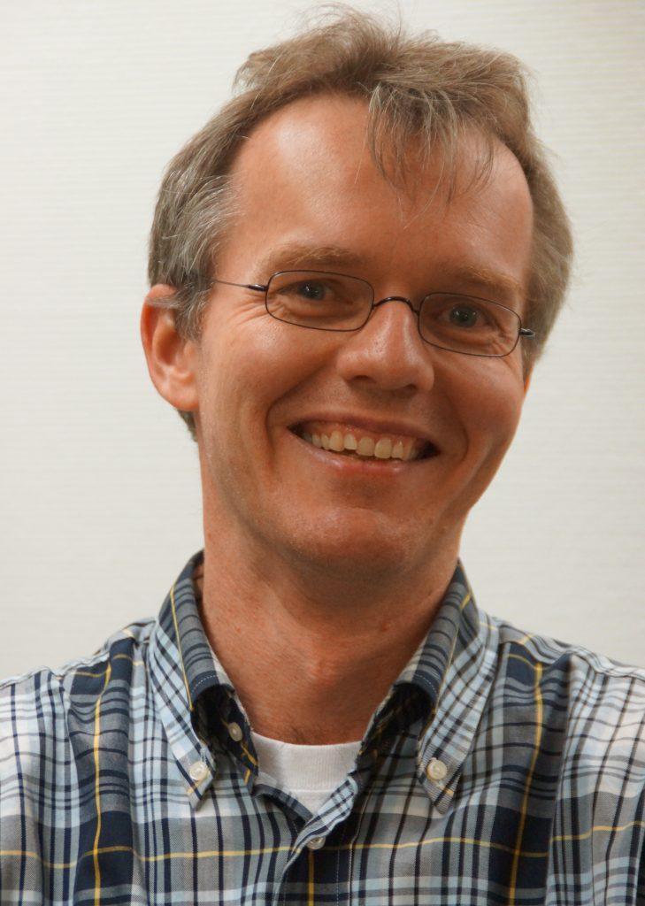 Smiling man with eyeglasses and plaid shirt.
