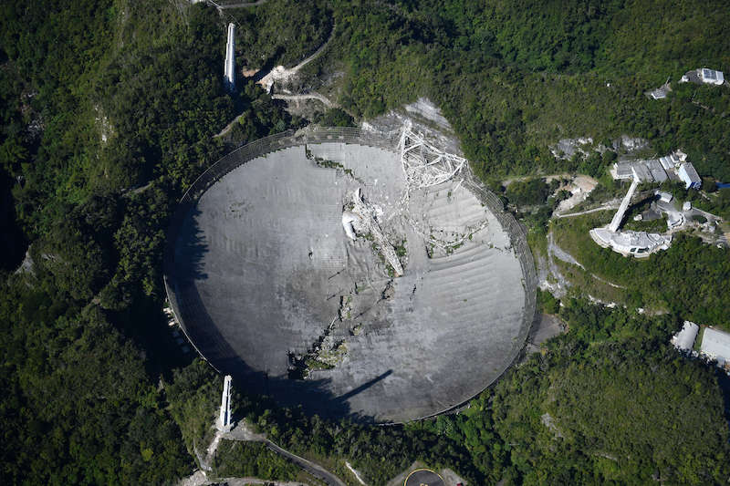 Aerial view of enormous dish with much damage across cneter and side.