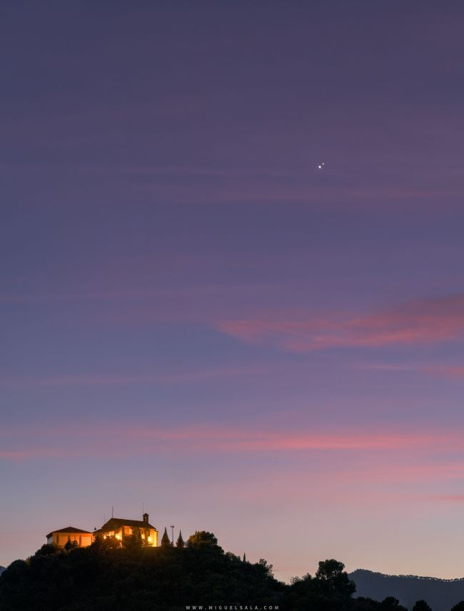 Two bright dots in pink sunset clouds above lighted house on hilltop.