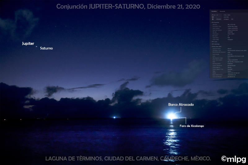 Bright dots of Jupiter and Saturn with a boat docking across a body of water under a deep blue sky.