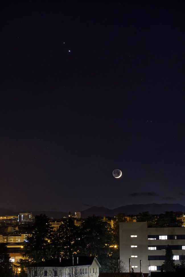 Crescent moon over buildings with two bright dots at top.