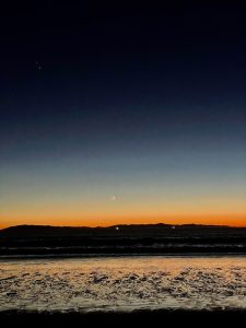 colourful horizon with a crescent below and two bright dots above.
