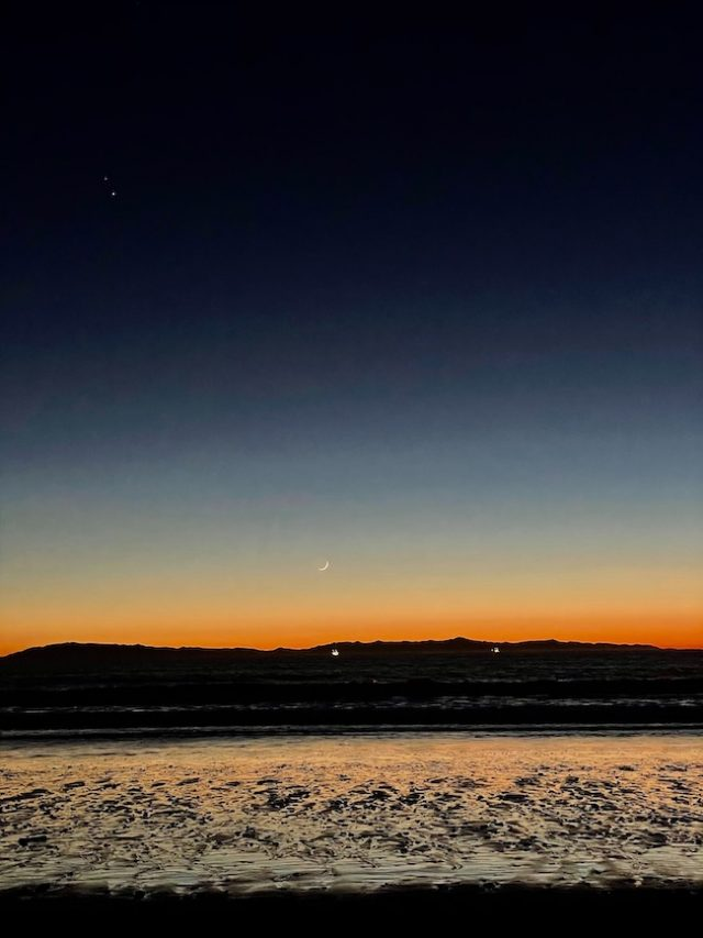 Orange-striped horizon with tiny crescent moon and two bright dots above in dark twilight.