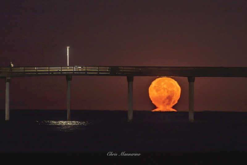 Moon rising over water under a bridge, sitting on a 'pedestal' of light.