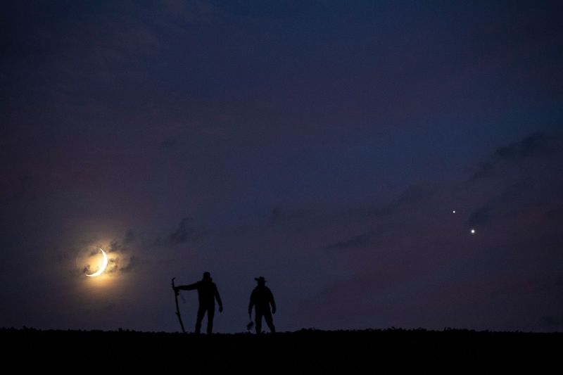 Two men silhouetted, one holding a staff, in front of low crescent moon in clouds, and two bright dots.