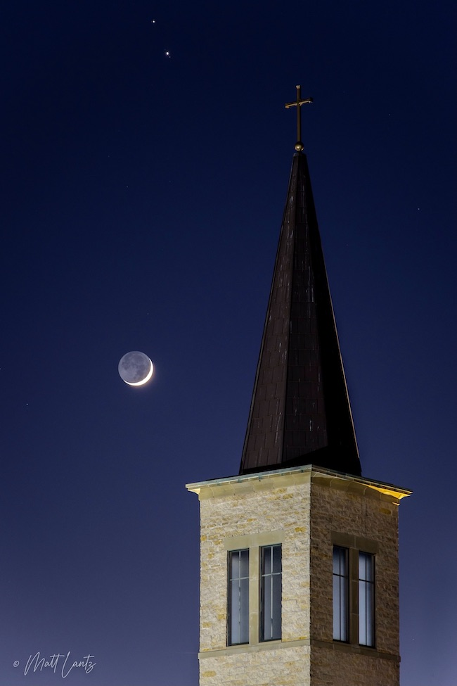Pointed church steeple in foreground, crescent moon - showing earthshine - and two bright dots in sky.