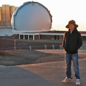 Man in hat and jacket standing outside observatory dome.