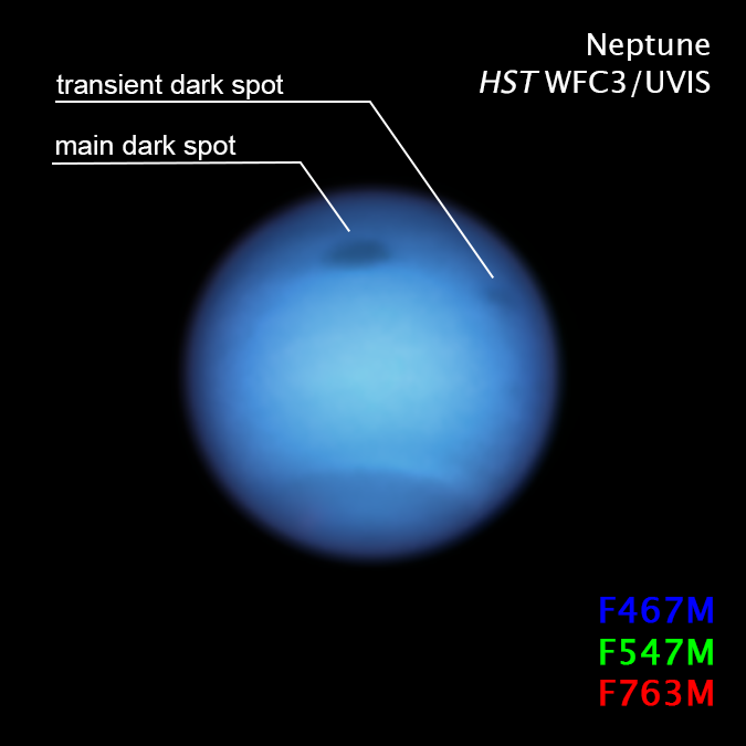 Large bluish planet with two labeled dark spots and text annotations, on black background.