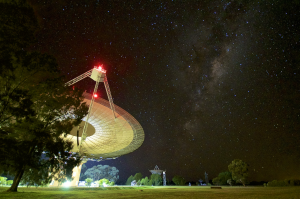 Radio telescope with lights on at night, and stars in the sky above.