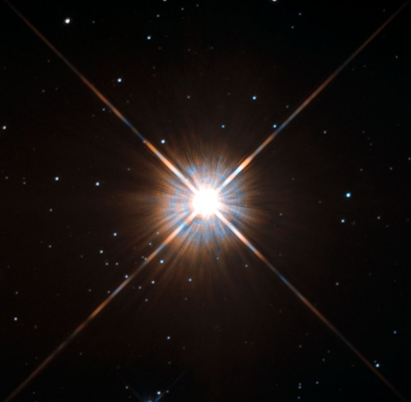 Bright central star with light refraction rays and other stars in background.