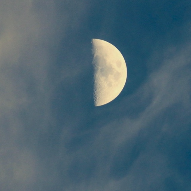 Vertical half circle on blue background with wispy white clouds surrounding it.