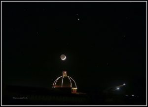 illuminated crescent over a church dome, with two bright spots above.