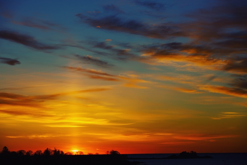Orange, yellow and red sky with faint but distinct yellow beam of light extending upward from horizon.