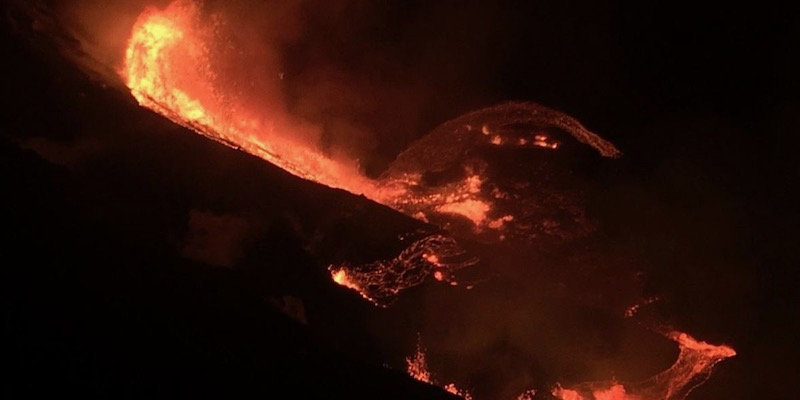 Night photo of glowing orange lava flowing down a mountainside, into a lava lake.