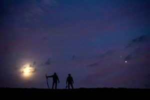 Dark silhouettes in front of low crescent and two bright dots.