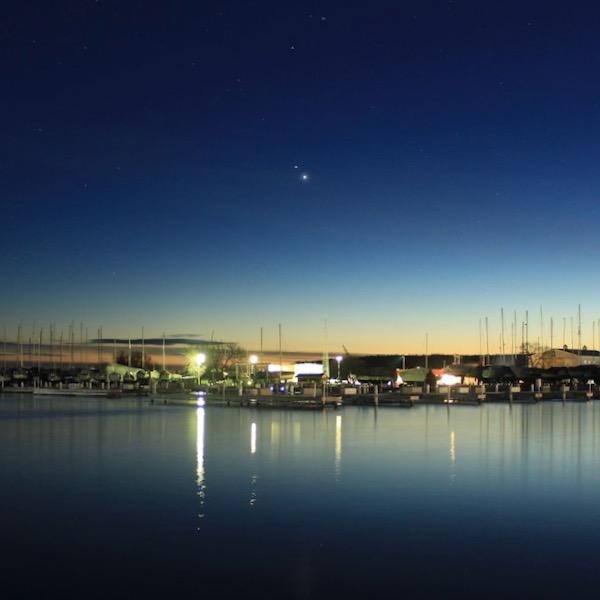 Jupiter and Saturn, close together at dusk, above a harbor.