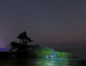 A picnic table and the Pacific Ocean in the foreground, a man looking upwards at Jupiter and Saturn near each other in the sky.