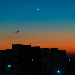 Silhouettes of buildings, background gradient of color from orange to blue with dark spots on left side and a crescent at the top and one white spot.