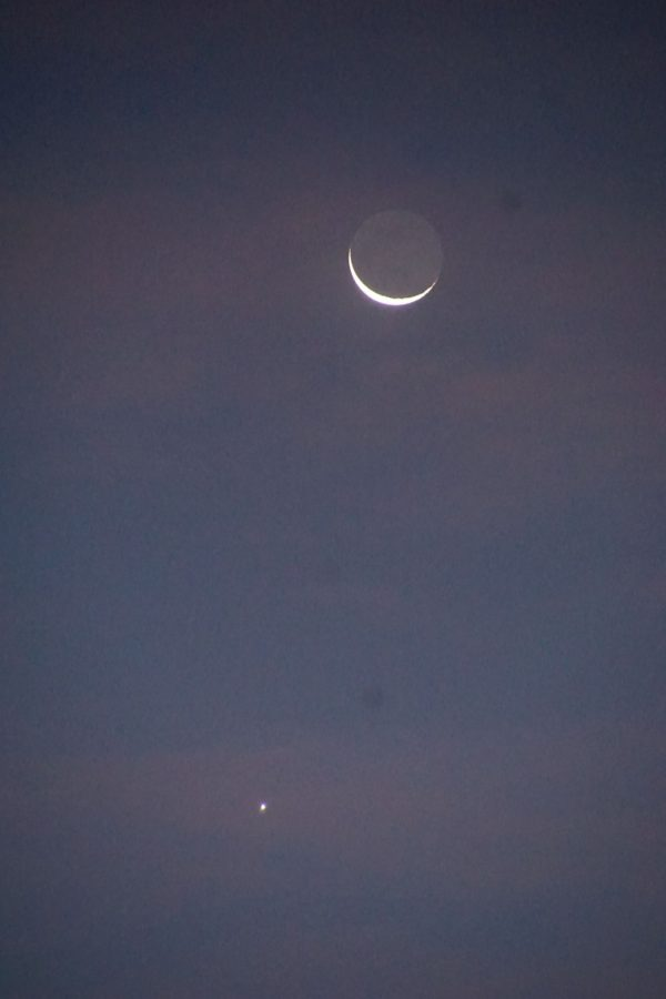 Thin crescent moon, with dark part slightly glowing, above slightly fuzzy bright dot of Venus.