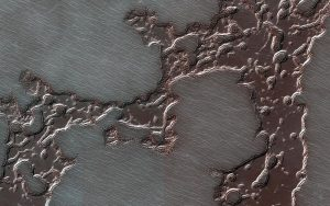 Dark splotch-like patches of frozen water-ice are pictured on the surface of Mars.