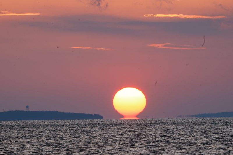Sunset over the ocean. The lower rim of the sun is spread out while the upper part of the sun remains a round disk: the sun resembles the Greek letter omega.