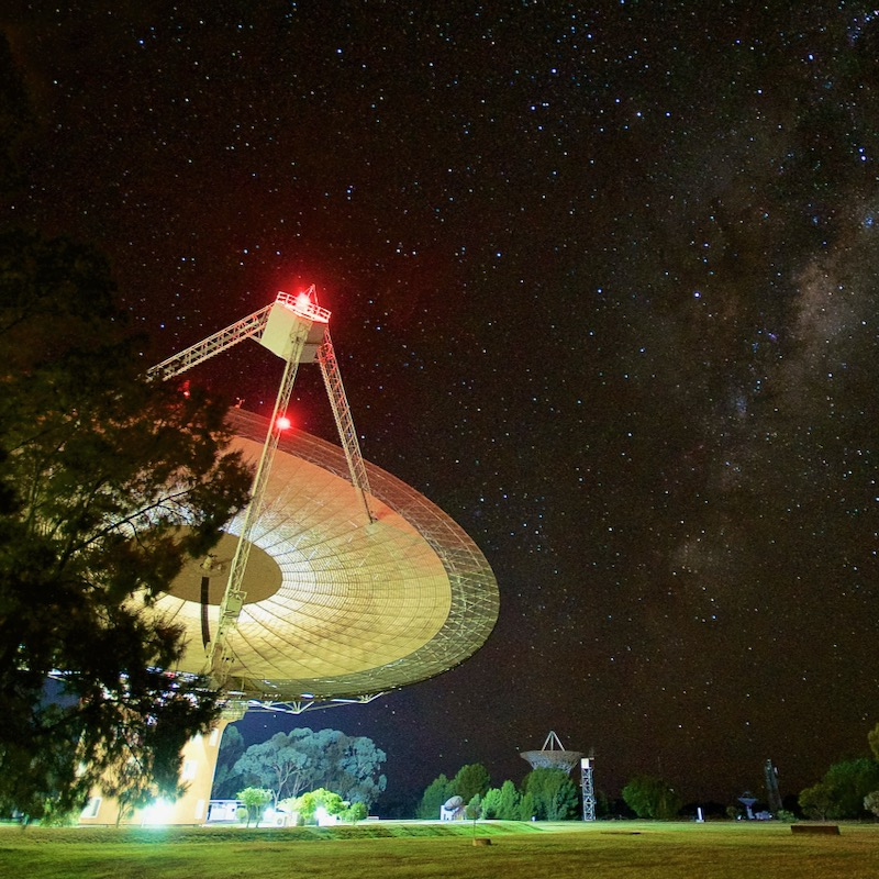 Dish-type radio telescope with lights on at night, and stars in the sky above.
