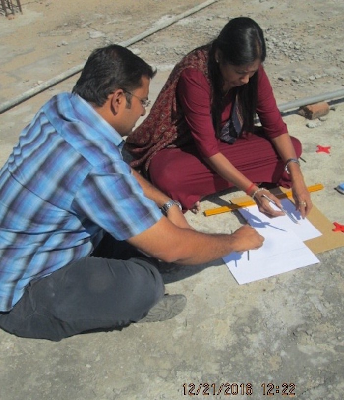 A man and a woman sitting on the ground measuring shadows on paper.
