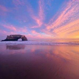 A beach at sunset, a stone arch on one side and streaky clouds above.